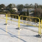 A rooftop guardrail installation using metal railings at the roof edge for maintenance personnel is an example of passive fall protection.
